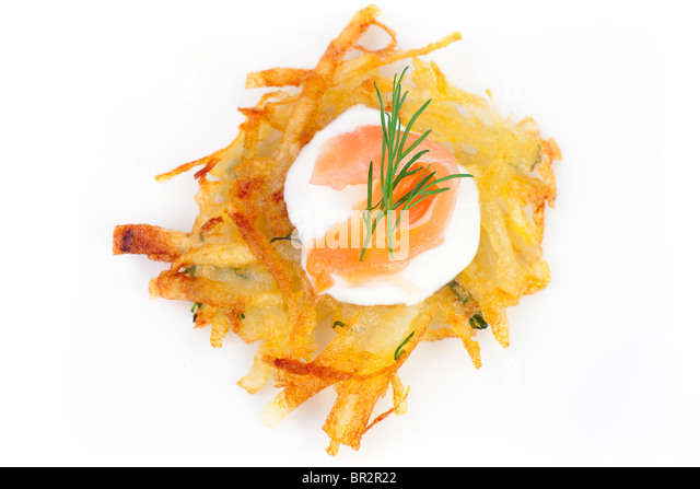 Bite sized potato rosti appetizer topped with fresh sour cream, smoked salmon and dill viewed from directly above - Stock Image