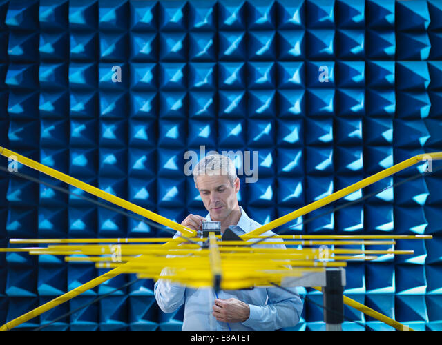 Scientist preparing to measure electromagnetic waves in anechoic chamber - Stock-Bilder
