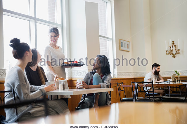 Woman serving friends at cafe table - Stock Image