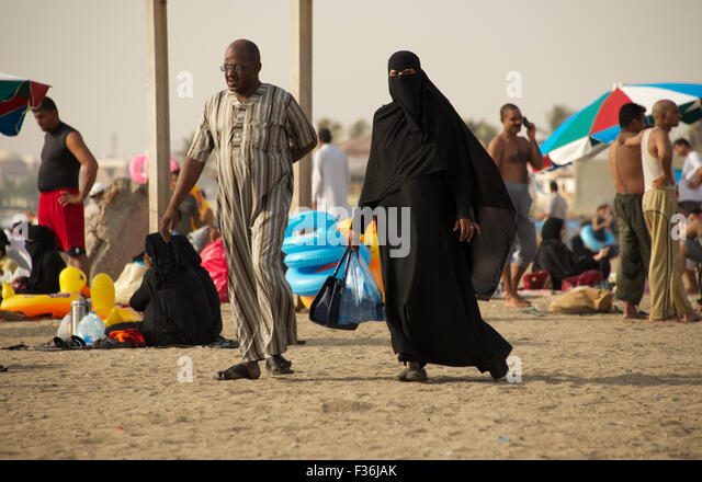 Muslim couple strolling on beach of the Red Sea in Jeddah, Saudi Arabia - Stock Image