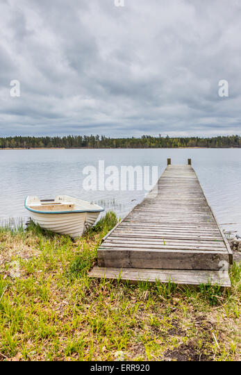 White Rowing boat Next to a Wodden Pier with a Cloudy Sky as Background - Stock Image