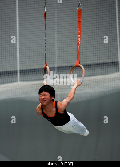 Young boy gymnastics with Roman rings - Stock Image