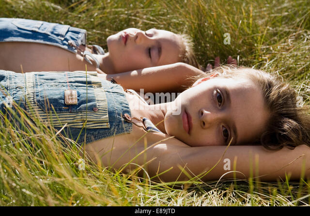 two girls in overalls laying in field - Stock-Bilder