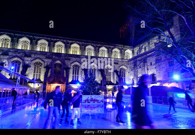 Skaters on the Ice Skating Rink in the grounds of Winchester Cathedral, Winchester, Hampshire UK where the annual - Stock Image