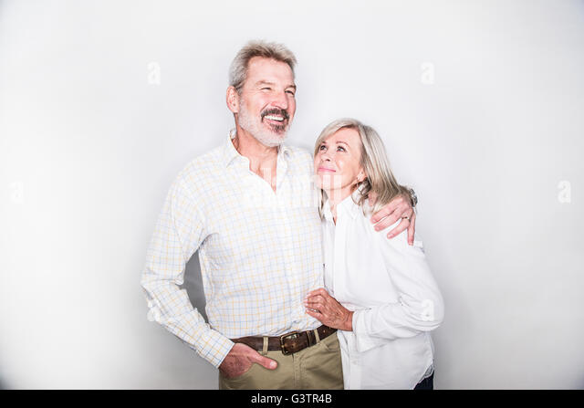 A mature couple posing in a studio looking happy. - Stock-Bilder