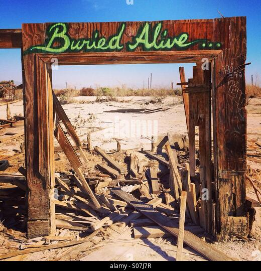 Buried alive sign on destroyed home - Stock Image