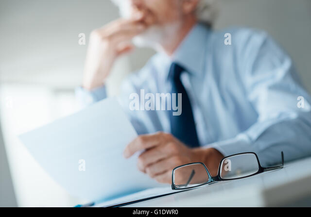 Pensive businessman with hand on chin looking away and holding a document, selective focus, glasses on foreground - Stock Image