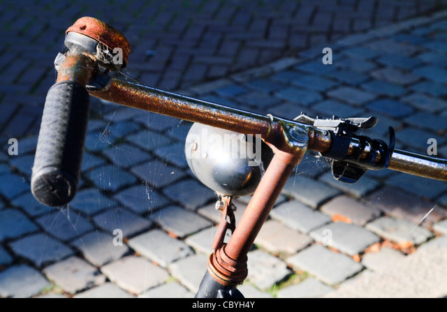 An old rusty dumped bicycle on a cobbled street - Stock-Bilder