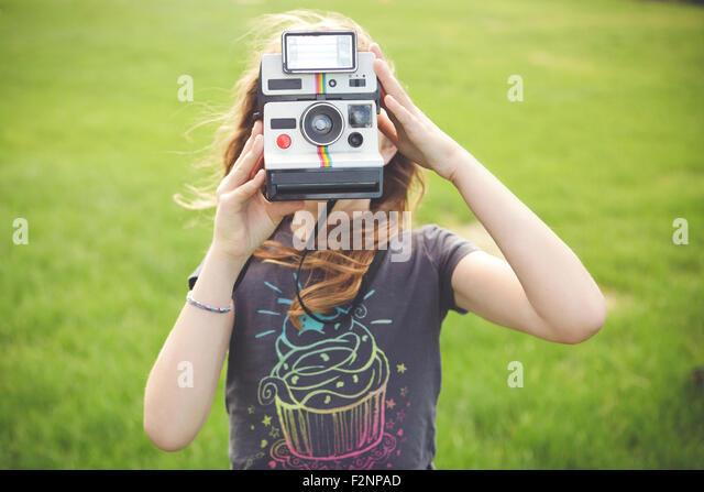 Caucasian girl taking instant photograph outdoors - Stock-Bilder