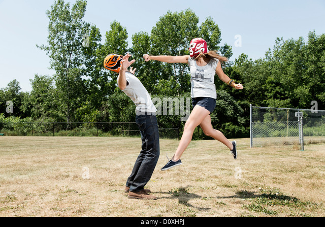 Couple wearing wrestling masks play fighting - Stock Image