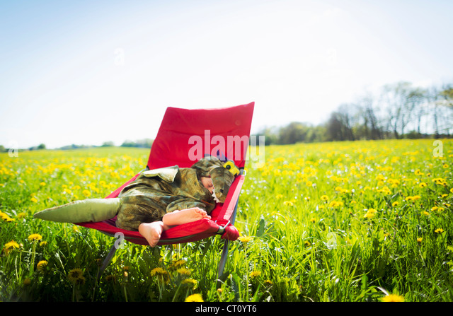 Boy in costume sleeping in chair - Stock Image