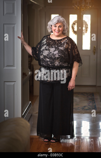 Portrait of well dressed mature woman in hallway - Stock Image