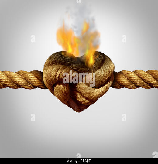 Divorce and separation concept as a rope with a burning knot shaped as a love heart as a relationship problem symbol - Stock-Bilder