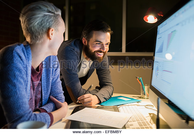 Graphic designers working late at computer in office - Stock-Bilder