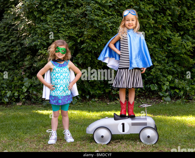 Young girls in capes playing dress up - Stock Image