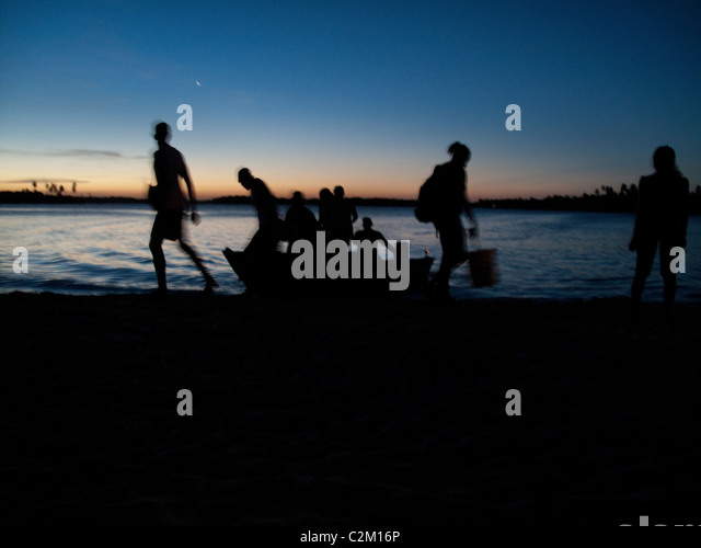 Group of young people arriving by boat at sunset on Boipeba Island, Bahia State, Brazil - Stock Image
