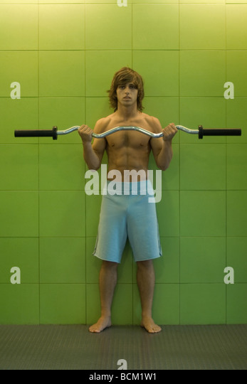 Young man lifting barbell, full length - Stock Image