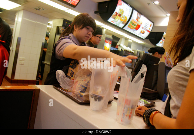 Hong Kong China Kowloon Sham Shui Po McDonald's fast food restaurant counter employee job Asian woman customer - Stock Image