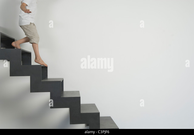 Germany, Low section of boy (4-5 years) moving down from stairs - Stock Image