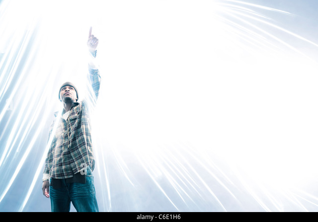 African American man pointing at light spark - Stock Image