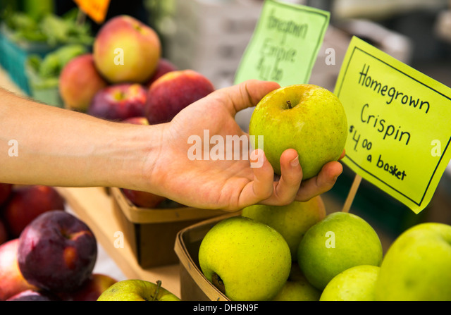A farm stand with fresh fruit on display.  A person selecting apples. - Stock Image