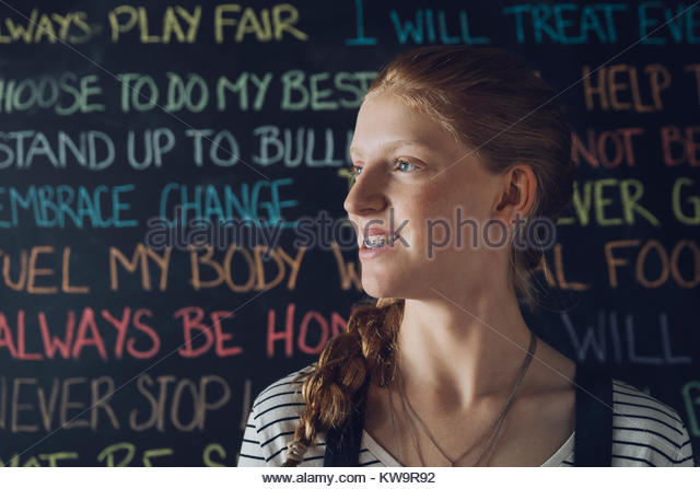 Portrait confident Caucasian tween girl looking away against wall with chalk text - Stock Image