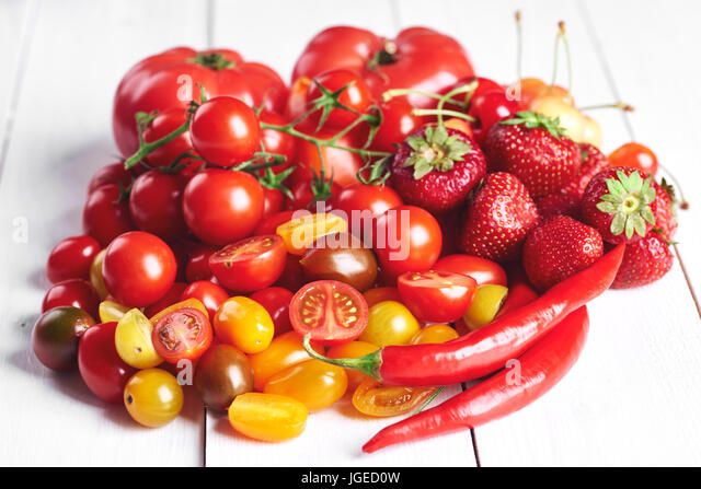 Red vegetables and fruit on white wood - Stock Image