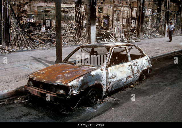Burned out car and shops - Stock Image