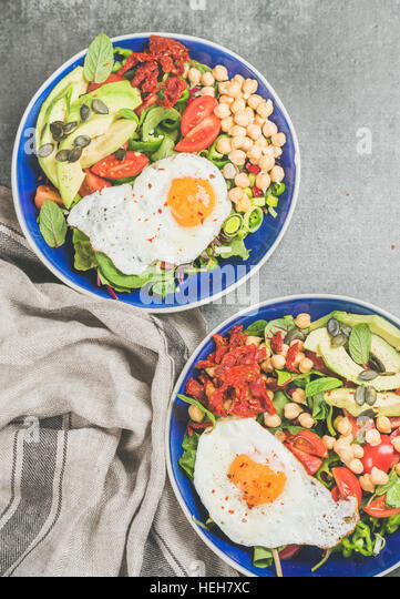 Healthy breakfast bowls with fried egg, chickpea sprouts, seeds, fresh vegetables and greens over grey concrete - Stock Image