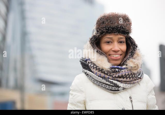 Portrait of happy woman in warm clothing outdoors - Stock Image