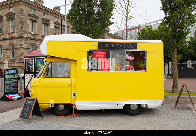 Yellow food truck of natural fruit juice and veggie food parked in the street - Stock Image