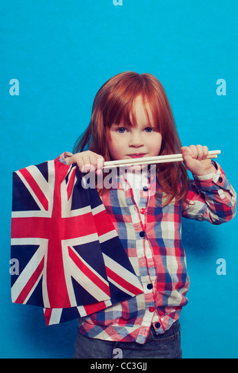 A young girl holding two British flags - Stock-Bilder