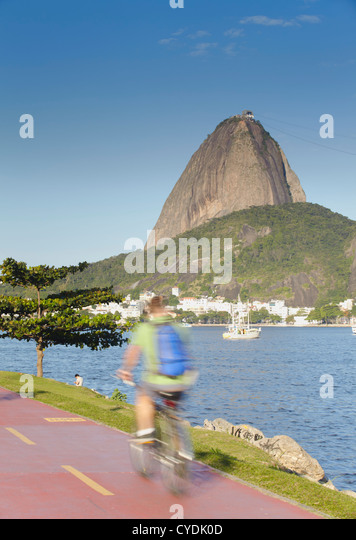 Cyclist on pathway around Botafogo Bay with Sugar Loaf Mountain (Pao de Acucar) in the background, Rio de Janeiro, - Stock Image