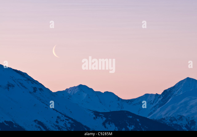 Cresent moon rises at dawn over the Kenai Mounatins along the Turnagain Arm, Southcentral Alaska, Spring - Stock Image