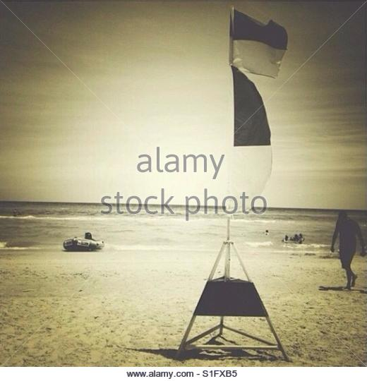 people at the beach near a Safety Flag and an Inflatable Rescue Boat' - Stock Image