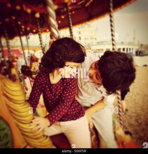 Brother and sister having fun on a merry-go-round / carousel in Brighton, England - Stock-Bilder
