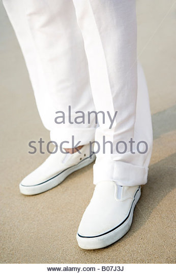 close up of a man's legs and feet on a beach - Stock Image