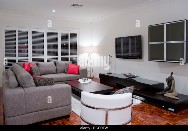 modern living room interior with charcoal sofa and chocolate brown coffee table and wide screen plasma TV. - Stock Image