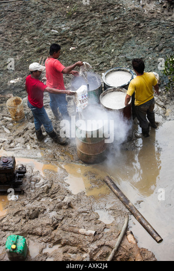 men people standing working emptying bags of powder into cans barrel chemicals solution in mud water sticks pipe - Stock Image