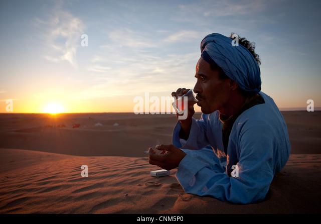 Nomad Berber drinking tea at sunset time in the Sahara Desert, Erg Chigaga, Morocco - Stock-Bilder