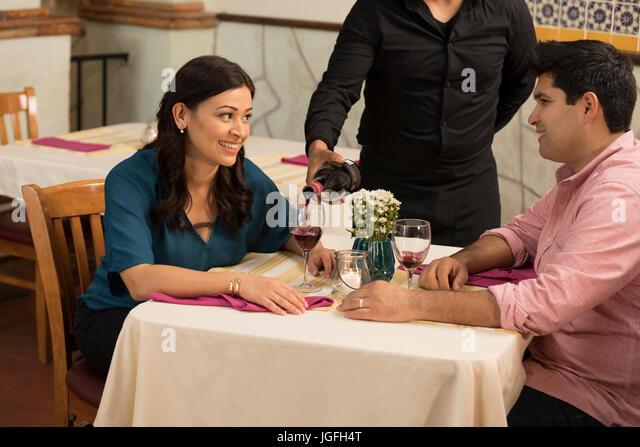 Waiter pouring wine for Hispanic couple in restaurant - Stock Image