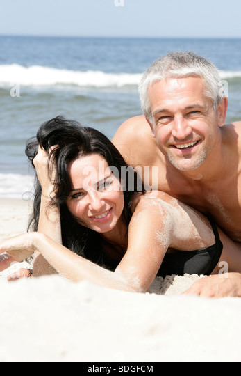 Attractive mature couple on the beach - Stock Image