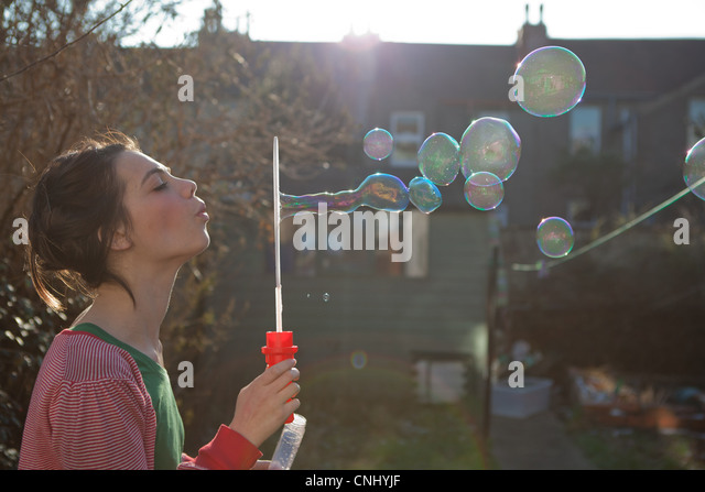 Young woman blowing bubbles outdoors - Stock-Bilder