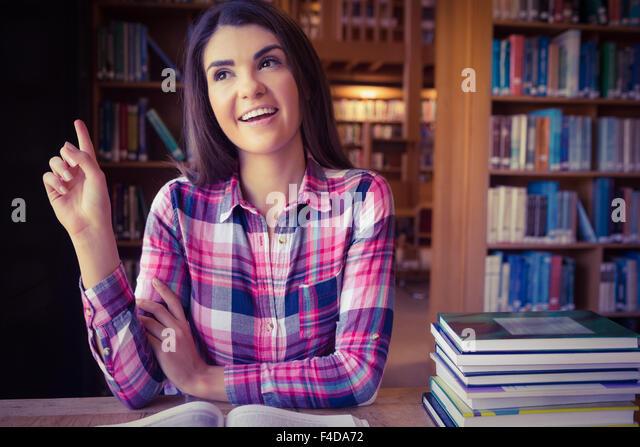 Happy female student at table against bookshelves - Stock Image