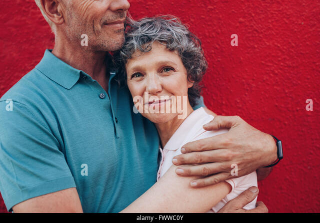Portrait of happy mature woman embracing her husband against red background. Affectionate couple together against - Stock Image