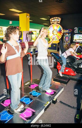 Indiana Valparaiso Inman's Fun and Party Center video game arcade girls teen play amusement fun jump hop motion - Stock Image