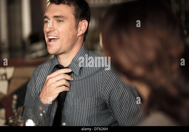 Businessman loosening tie in a wine bar - Stock-Bilder