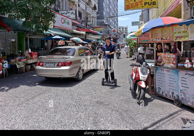 Man delivering food using a hoverboard. Thailand street scene, S. E. Asia. - Stock Image