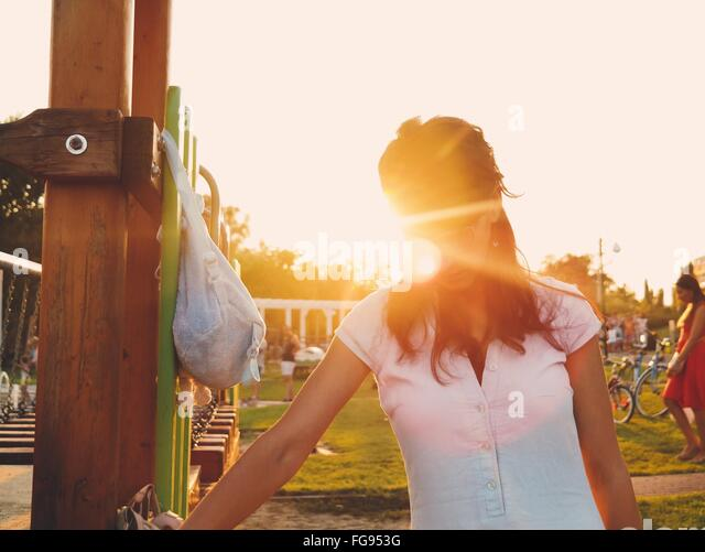Woman Standing In Park Against Sky On Sunny Day - Stock Image