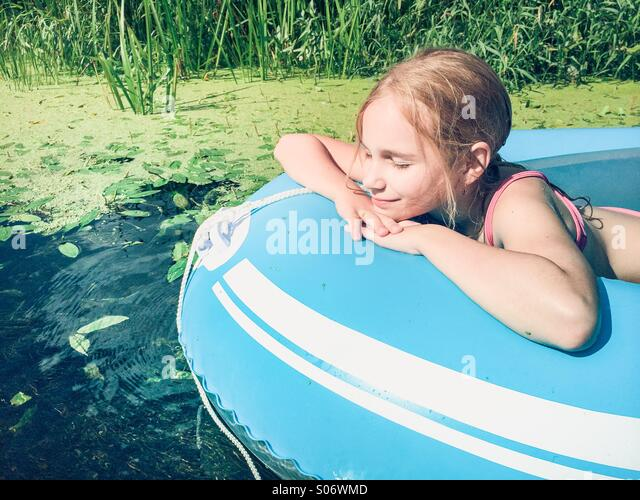 Little girl sitting in a raft on a river with lush greenery - Stock-Bilder